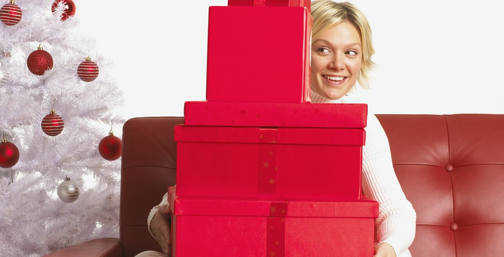 Young Woman Sitting on Sofa with Assorted Presents on Lap